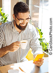 Happy delighted man enjoying his cup of coffee