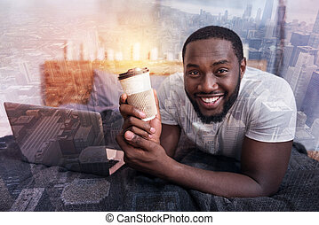 Happy delighted man holding a cup of coffee