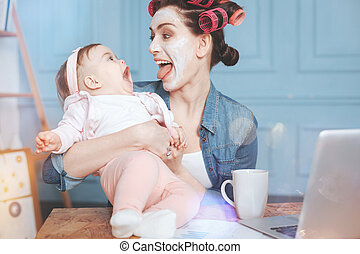 Happy delighted woman having fun with her daughter