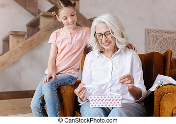 Happy delighted woman holding a gift box
