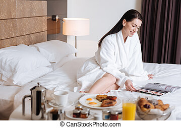 Happy delighted woman reading a magazine - Before breakfast....