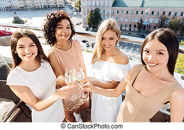 Happy delighted women raising their glasses