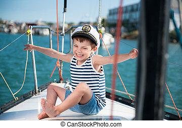 happy delightful kid in captain cap sitting on luxury yacht board in summer day