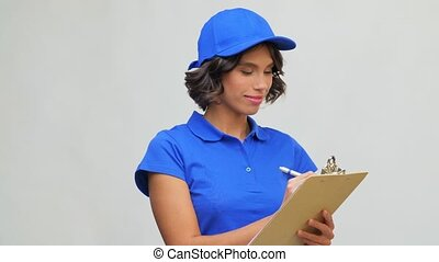 happy delivery girl with clipboard and pen writing - mail ...