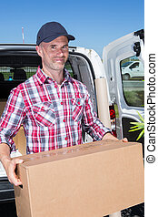 happy delivery man carrying box in front of a truck