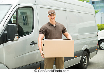 Delivery Man Holding Box - Happy Delivery Man Holding Box In...