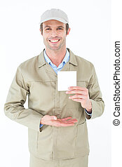 Happy delivery man showing blank note