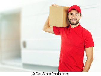 happy delivery man with box on shoulder in front of a truck