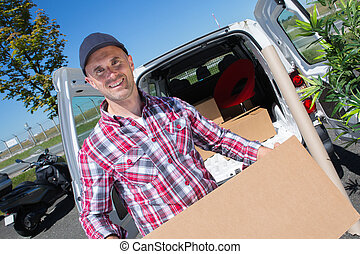 happy delivery man with cardboard box by his van