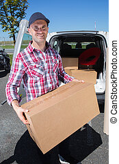 happy delivery man with cardboard boxes in front van