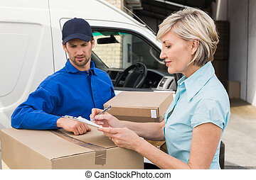 Happy delivery man with customer outside the warehouse