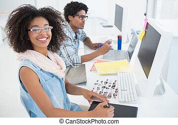 Happy design team working at desk in their office