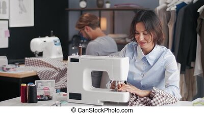 Happy designer's couple working on sewing machines at own little atelier. Professional fashion people designing trendy clothing at studio.