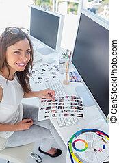 Happy designer holding contact sheet