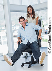 Happy designers having fun with a swivel chair in their...