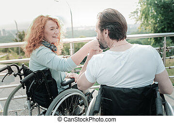Happy differently abled couple sitting on their wheelchairs