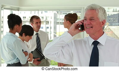 Happy director on the phone with employee in background in a...