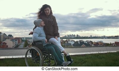 Happy disabled man in a wheelchair embraces with young woman...