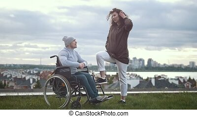 Happy disabled man in a wheelchair embraces with young woman outdoors