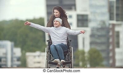 Happy disabled man in a wheelchair with happy young woman...