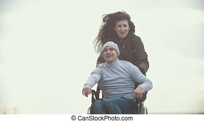 Happy disabled man in a wheelchair with happy young woman running at the city street