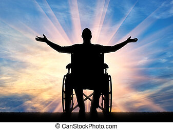 Happy disabled man in a wheelchair with arms raised up