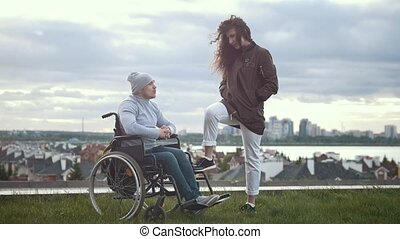 Happy disabled man in a wheelchair with woman talking on the hill