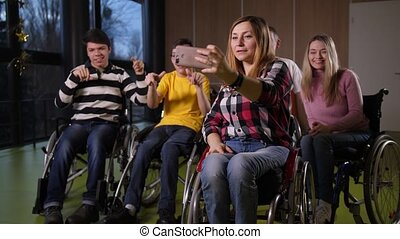 Happy disabled people in wheelchairs making selfie