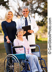 happy disabled senior woman on wheelchair and daughter meeting retirement village doctor outdoors