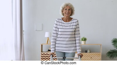 Happy disabled senior woman stand hold walker looking at camera