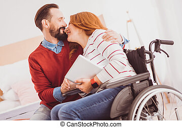 Happy disabled woman kissing her man