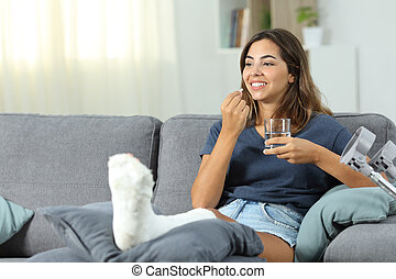Happy disabled woman taking a painkiller pill