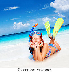 Happy diver woman lying down on beautiful sandy beach, ...