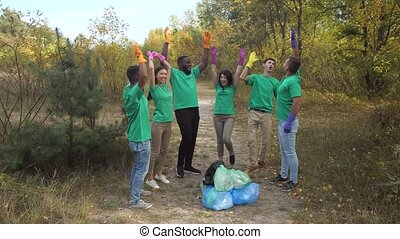 Happy diverse activists high five after trash collection