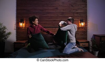 Happy diverse boys beating each other with pillows - Joyful ...