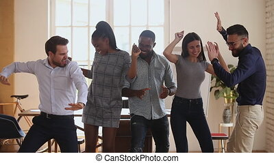 Happy diverse business people dancing at office, celebrating corporate achievement.