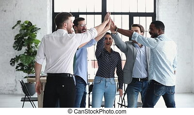 Happy diverse business team give high five together, slow motion