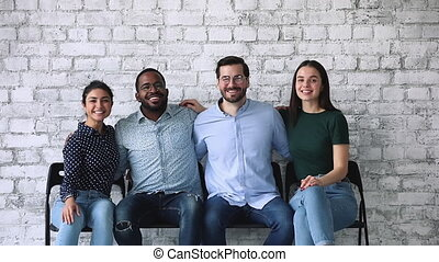 Happy diverse business team looking at camera sit on chairs