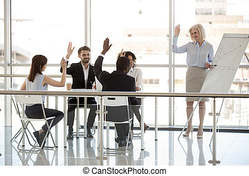Happy diverse businesspeople and coach raising hands at office t