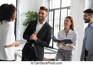 Happy diverse colleagues talking, standing in modern office room