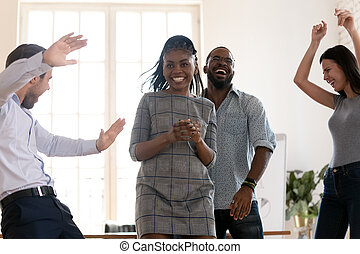Happy diverse employees dance celebrating success in office