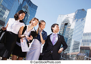 Happy diverse group of executives pointing over business center. Outdoor
