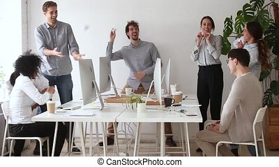 Happy diverse office workers having fun throwing crumpled paper balls