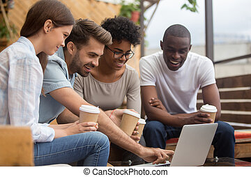 Happy diverse young friends looking at laptop on cafe terrace