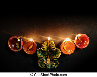 Happy Diwali. Background picture of traditional diya clay oil lamp lit at dark night on Diwali with copy space in landscape format.