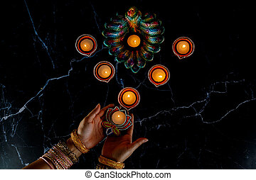 Happy Diwali - Woman hands with henna holding lit candle isolated on dark background.