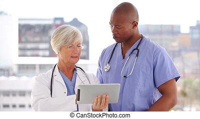 Happy doctor and nurse looking at a tablet pc