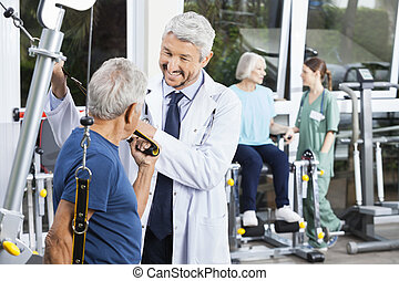 Happy Doctor Assisting Senior Man With Resistance Band