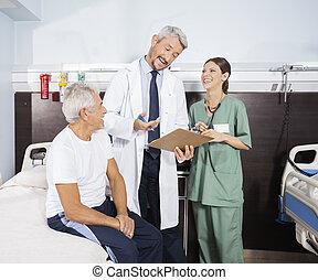 Happy Doctor Explaining Report To Senior Patient In Rehab Center