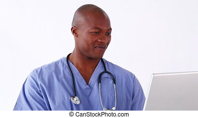 Happy doctor holding a laptop